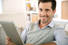 Happy man sitting in couch looking at tablet Royalty Free Stock Image