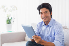 Happy man sitting on couch using tablet pc Royalty Free Stock Images