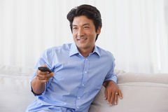 Happy man sitting on couch watching tv Royalty Free Stock Photo