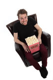Happy man sitting down with a popcorn bucket Stock Image
