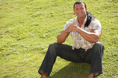 Happy man sitting on the field Stock Photo