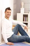 Happy man sitting on floor at home Stock Image