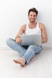 Happy man sitting on floor with laptop Stock Photos