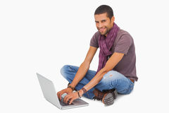 Happy man sitting on floor using laptop Stock Photography