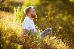 Happy man sitting on the grass and dreaming Royalty Free Stock Photos