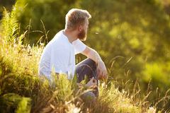 Happy man sitting on the grass Stock Image