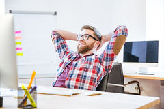 Happy man sitting with hands behind head and relaxing Stock Photo