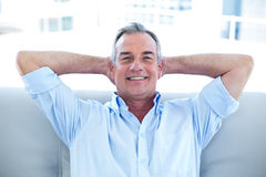 Happy man sitting with hands in hair at home Stock Photography