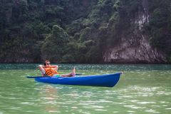 A happy man sitting in a kayak boat on a lake relaxing royalty free stock photos