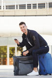 Happy man sitting on luggage with cellphone waiting Stock Photography