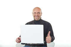 Happy man sitting at office desk with a laptop Stock Images
