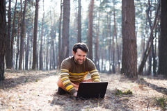 Happy man sitting outdoors using a laptop computer. A Happy man sitting outdoors in the sunny forest using a laptop computer Royalty Free Stock Photography