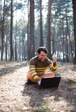 Happy man sitting outdoors using a laptop computer Stock Image