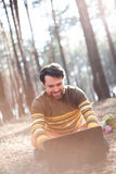 Happy man sitting outdoors using a laptop computer Royalty Free Stock Photo
