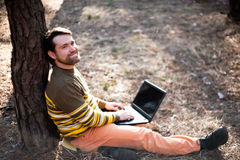 Happy man sitting outdoors using a laptop computer Stock Photo