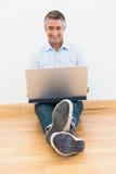 Happy man sitting on parquet using laptop Stock Photo
