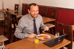 Happy man sitting in restaurant with laptop Royalty Free Stock Photography