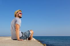 Happy man sitting by the sea with hat Stock Image