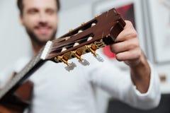 Happy man sitting on sofa. Focus on guitar. Royalty Free Stock Image