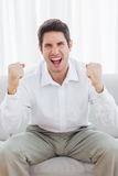 Happy man sitting on sofa has success Royalty Free Stock Image