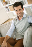 Happy man sitting in sofa at home Stock Images