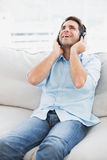 Happy man sitting on sofa listening to music Royalty Free Stock Photography