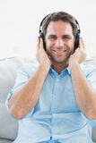 Happy man sitting on sofa listening to music smiling at camera Royalty Free Stock Image
