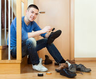 Happy man sitting on stairs and cleaning footwear Royalty Free Stock Photos