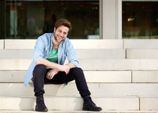 Happy man sitting on steps outdoors. Portrait of a happy man sitting on steps outdoors royalty free stock images