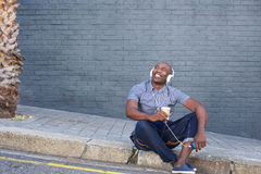 Happy man sitting by a street and listening to music Stock Image