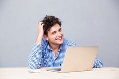 Happy man sitting at the table with laptop royalty free stock photos