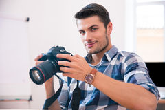 Happy man sitting at the table with photo camera Royalty Free Stock Photos