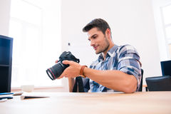 Happy man sitting at the table with photo camera Stock Photos
