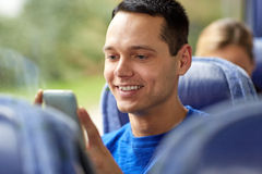 Happy man sitting in travel bus with smartphone Stock Images
