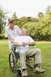 Happy man sitting in a wheelchair talking with his nurse pushing Stock Images