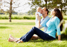 Happy man sitting with wife and kissing little son. Happy young Caucasian men and his wife sitting together on grass, holding little son and kissing him. Family Royalty Free Stock Images