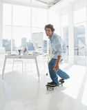 Happy man skateboarding in a bright office Stock Photo