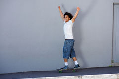 Happy man skateboarding outside with arms raised Stock Images