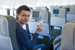 Happy man with small model airplane inside a large aircraft Stock Photography