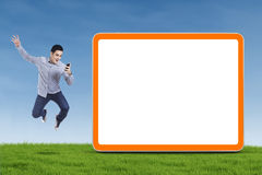 Happy Man with Smartphone. Happy asian man holding smartphone and jumping next to blank board royalty free stock photo