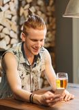 Happy man with smartphone drinking beer at bar Stock Photography