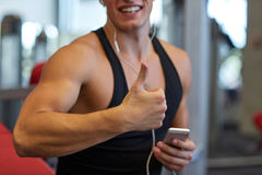 Happy man with smartphone and earphones in gym Stock Photo