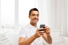 Happy man with smartphone at home royalty free stock photo