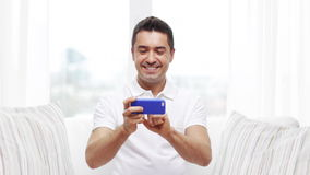 Happy man with smartphone at home stock video