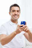 Happy man with smartphone at home Stock Image