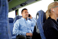 Happy man with smartphone and laptop in travel bus Stock Photo