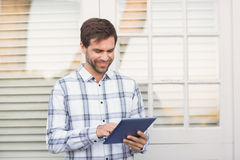 Happy man smiling at camera holding tablet Royalty Free Stock Photography