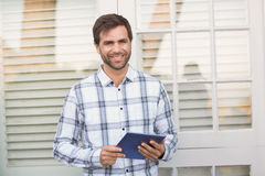 Happy man smiling at camera holding tablet Stock Image