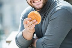 Happy man smiling at the cheeseburger - close up shot. Happy man with a cheeseburger, smiling. Dressed with Grey top and a hat. Blurred background Royalty Free Stock Photo