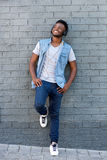 Happy man smiling with headphones leaning against wall Stock Photo